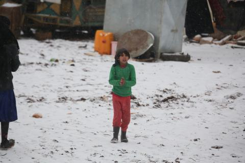 a girl stands in mid snow in a camp