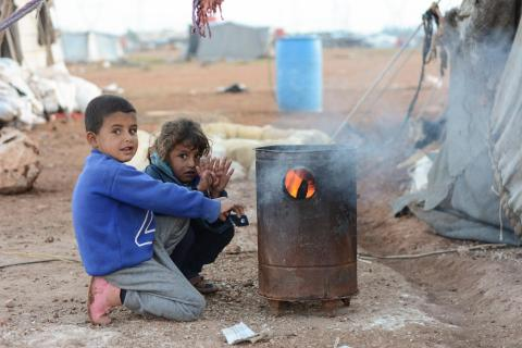 Two children seeking warm in the open from fire