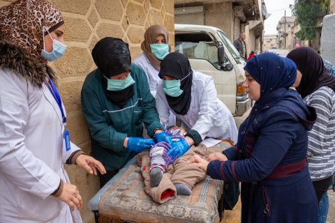 group of health workers giving child vaccine while women next to them