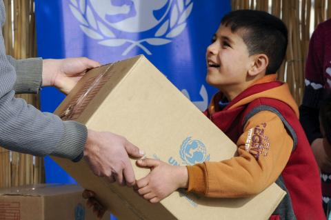 happy child carrying a UNICEF box