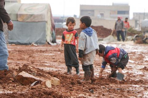 children standing among mud