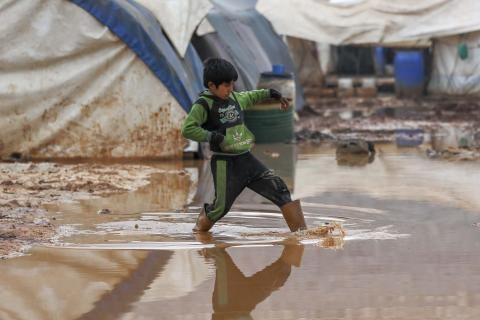 a child in a camp making his water through a muddy water lake