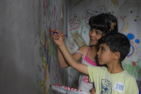 Two children drawing on wall