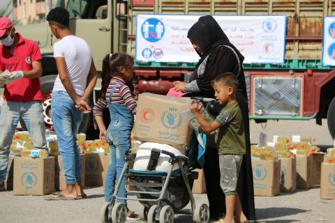 woman and children checking received food and hygiene items