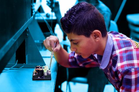 child practicing electronics repairmen