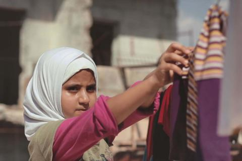 little girl hanging washed clothes