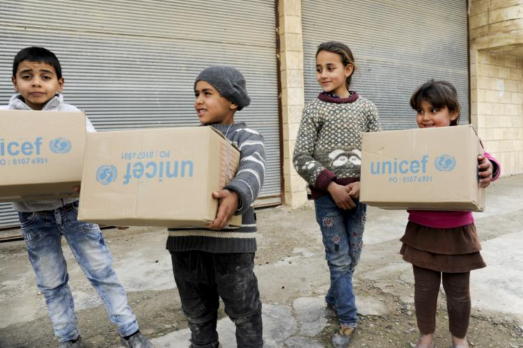 children carrying UNICEF boxes