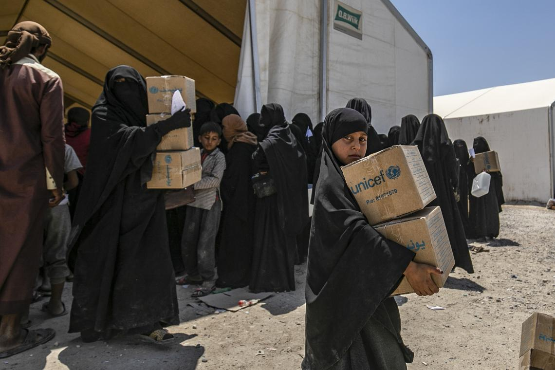 women and children carrying UNICEF boxes