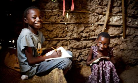Two children (a boy and a girl) writing in notebooks