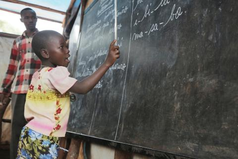 Young girl in semi-permanent classroom reciting words from the board.