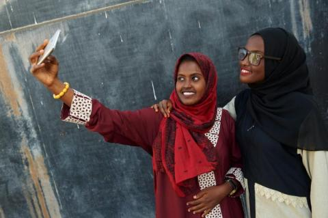 "Adolescent girls take a selfie with their smartphone at a ""Lifeskills"" event"