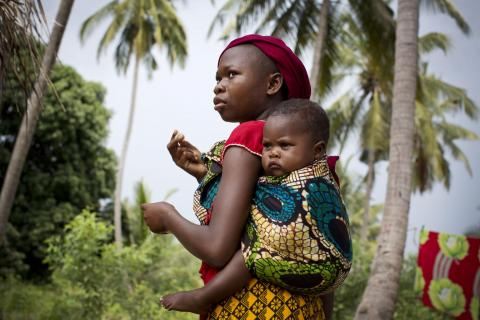 A young girl poses for a photograph with a baby on her back