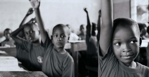Students in a class room with hands raised