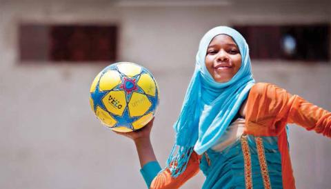 Adolescent girl holding a soccer ball