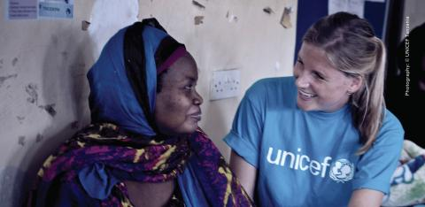 A UNICEF employee sits with a woman
