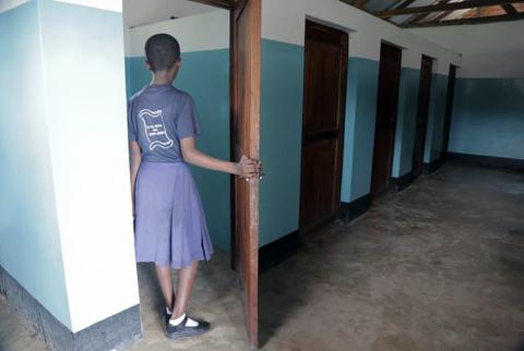 An adolescent girls opens a door to a toilet stall