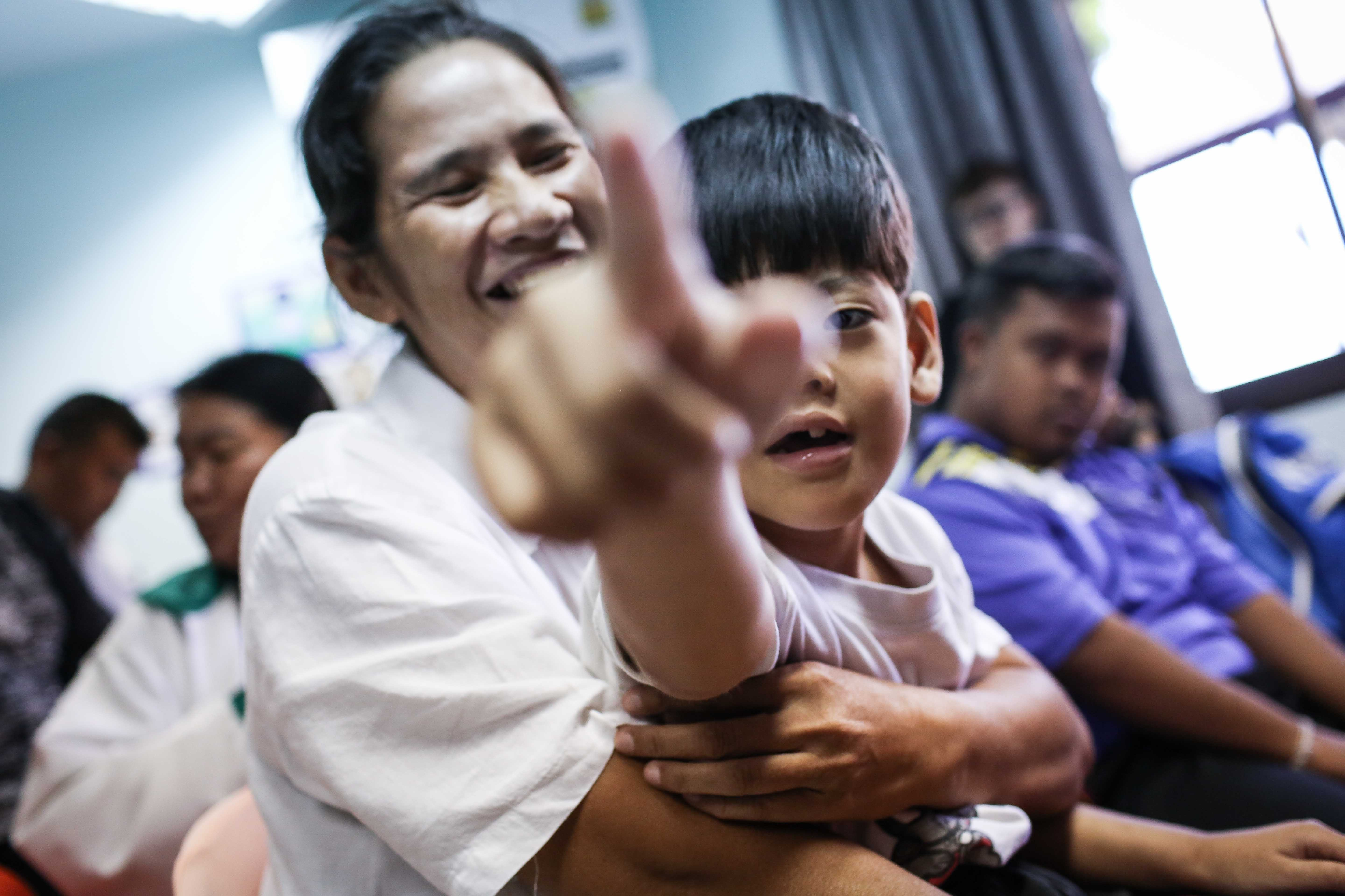 A child with intellectual disabilities is sitting on his mother's lap and is pointing toward the camera.
