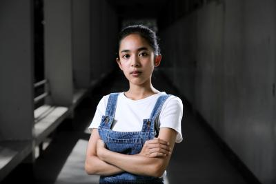 Mint - a young girl wearing a white t-shirt and a jeans overalls with her arms crossed.