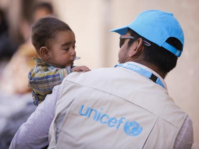 UNICEF child protection specialist is holding a 6-months-hold baby in his hands.