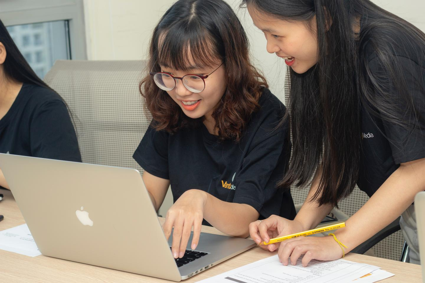 2 young women are working together, looking at the screen of the MacBook on the desk.