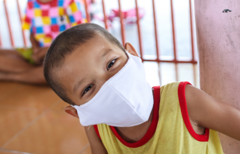 A boy wearing a white facial mask.