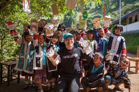 UNICEF staff is standing with a group of hilltribe children