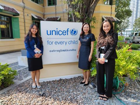 UNICEF Representative for Thailand and the two young female youths stand in front of the UNICEF logo at UNICEF Thailand office.