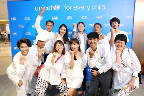 Some of the artists for the Art for The Future taking picture in front of UNICEF backdrop