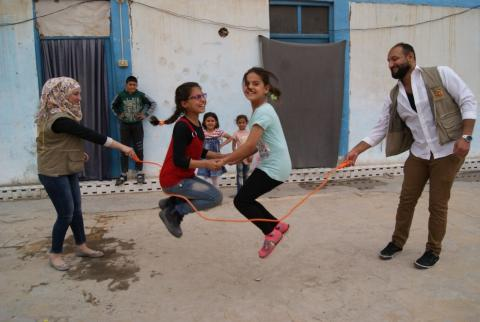 Alaa (in red), plays with UNICEF-supported volunteers and her sister Walaa
