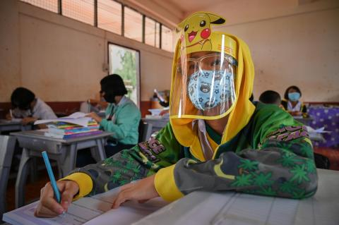 A student wearing a face shield is taking note in the classroom.