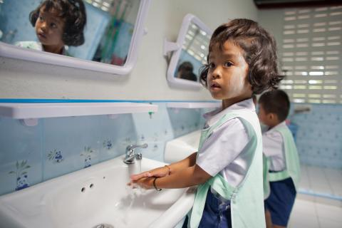A little girl in a student uniform is washing her hands at the basin.