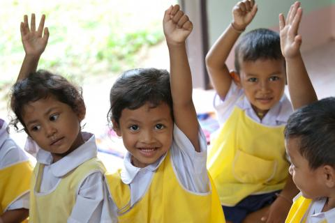 A group of young children wearing a yellow clothes over their student uniform are raising their hands, smiling.