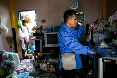 A middle-age man taxi driver in a blue shirt is standing, drinking a cup of water in his house