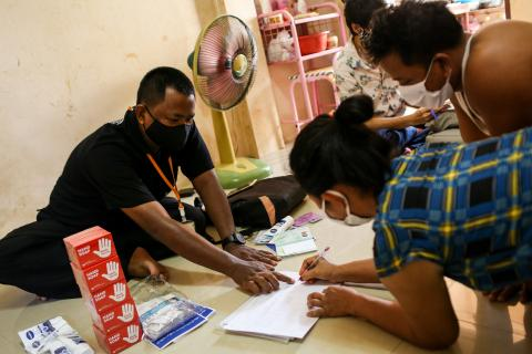 A man in a black polo shirt is guiding a women to write something on a paper