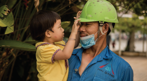 A worker wearing lime green helmet is carrying his son in his hand. The boy is touching his helmet.