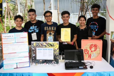 The 4 members from the Fantastic Four, the winning team of UNICEF's global Generation Unlimited Youth Challenge, and their guardian are standing behind the table where their ideas are displayed for the visitors.