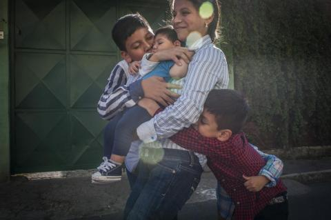 A mother and her three sons in Guatemala. The mother is holding one of her son while the other two are hugging her.