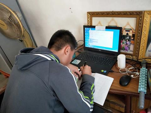 A boy joins an online learning session at his home