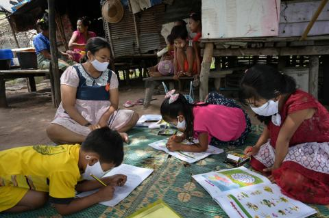Three little boys and girls are studying in the community instead of a classroom. This is because of the school closure during COVID-19 pandemic.