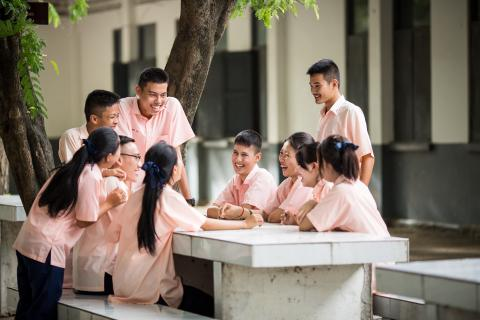 A group of students in student uniform are having a conversation happily.