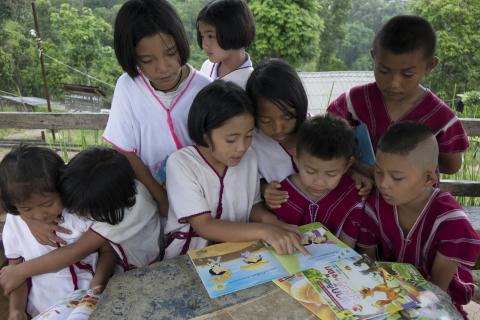 A group of hilltribe children are reading books from mobile library