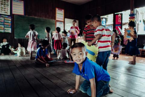 A young boy is crouching on the wooden floor in his English classroom at the Early Childhood Development Centre