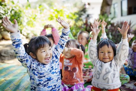 A group of young children are happily raising their hands.