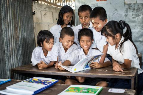 A group of students are reading a book together.