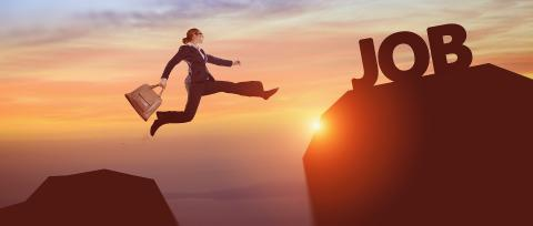 "A business lady holding a bag is jumping over a cliff to reach the word ""Job""."