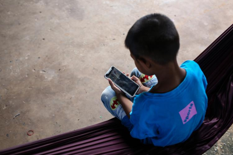 A boy in Khon Khaen Province spends time on his mobile phone during the COVID-19 pandemic.