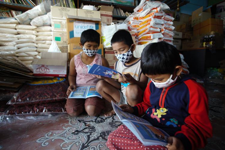 Young myanmar children are reading information booklets from UNICEF and partners.