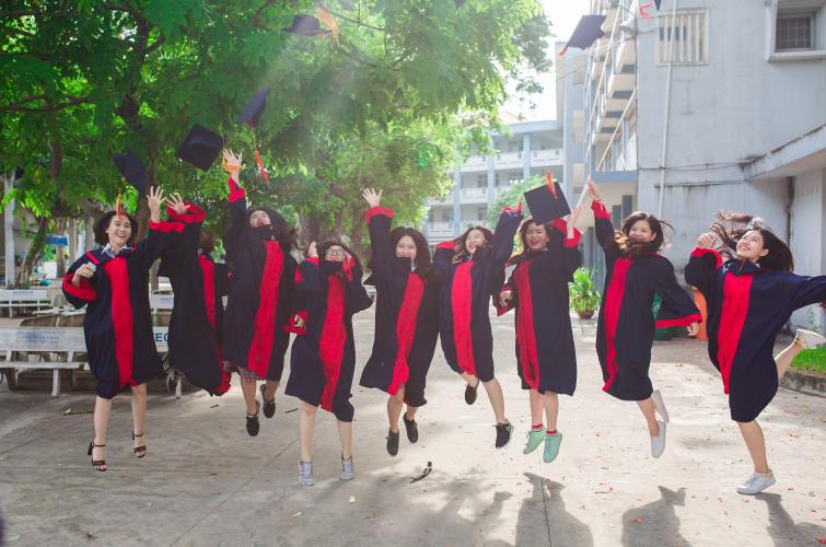 A group of graduated students are jumping happily after the graduation ceremony