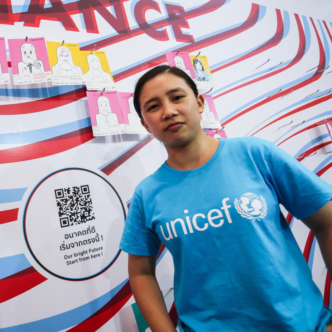 A young lady wearing UNICEF cyan blue t-shirt standing in front of a colorful backdrop.