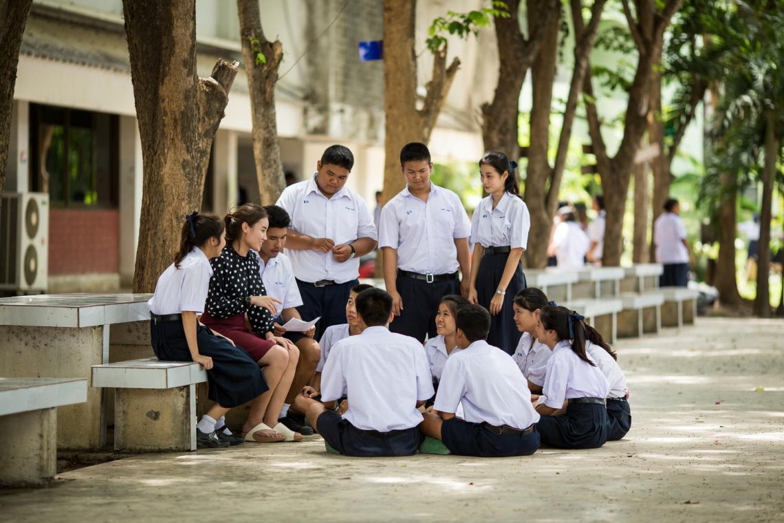 กลุ่มนักเรียนชายและหญิงกำลังห้อมล้อมคุณครู เพื่อพูดคุยกัน ในสวนของโรงเรียน